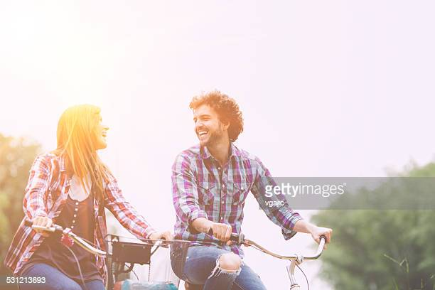 Fröhliche paar Reiten Fahrräder zusammen.