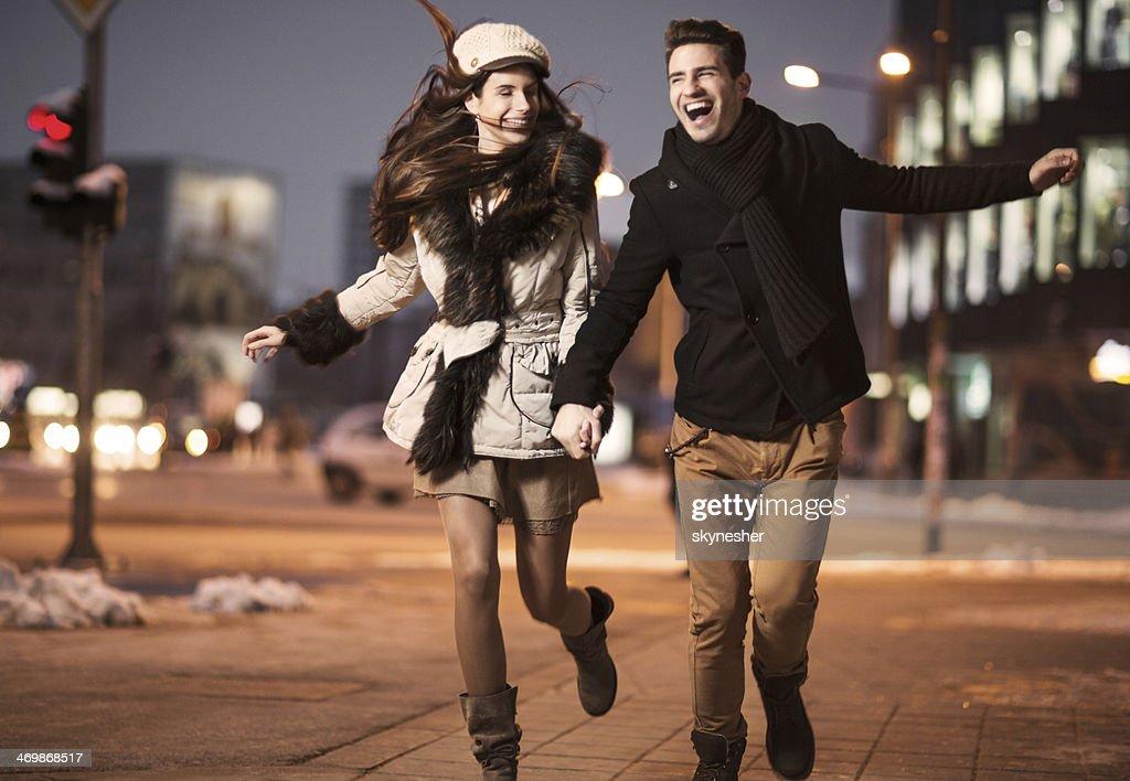 Cheerful couple running in the street. : Stock Photo