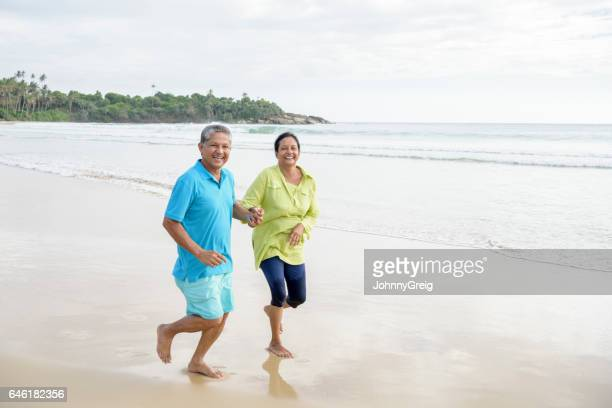 Cheerful couple running on beach smiling towards camera