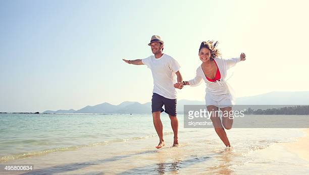 Cheerful couple running on the beach during summer.