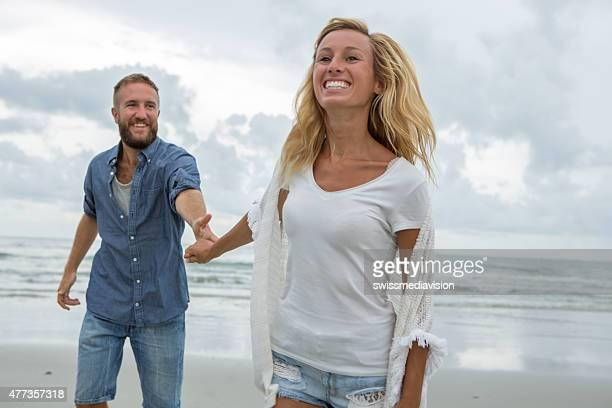 陽気なカップルはビーチでランニング