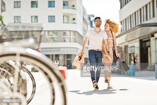 cheerful couple shopping and walking by the street