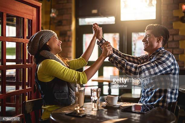 Cheerful couple sitting in a cafe and having fun.