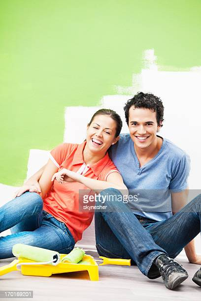 Cheerful couple sitting on floor after painting