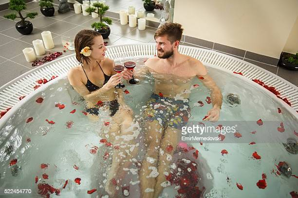Cheerful couple toasting with wine in a hot tub