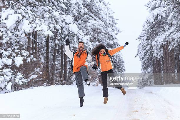 Cheerful couple tourists having fun in snow forest