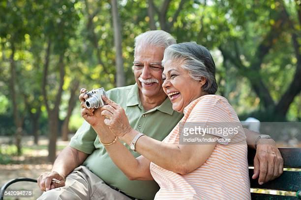 Cheerful couple using digital camera at park