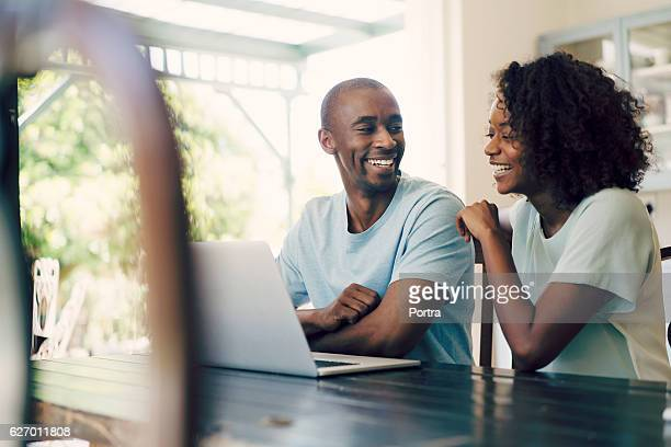 Cheerful couple using laptop at home