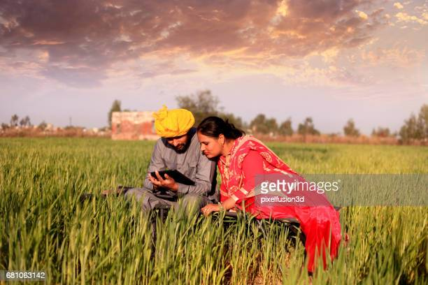 Cheerful couple using ipad in the nature