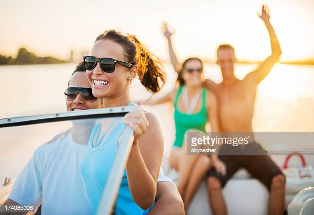 Cheerful couples enjoying on a speedboat ride.