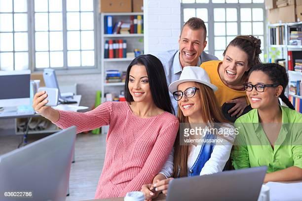 Cheerful coworkers making selfie in modern office