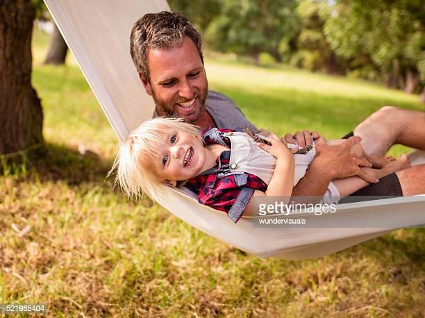 Joyeux parents câlins fils fils sur un hamac blanc