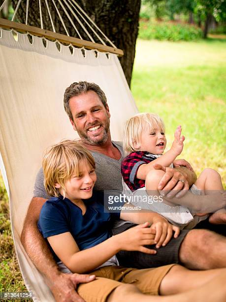 Cheerful dad hugging his two sons on hammock outside