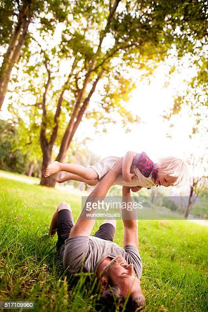 Cheerful dad playing with his toddler son in nature