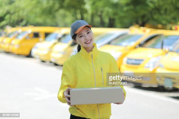 Cheerful delivery woman carrying carton