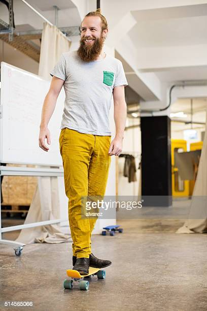Cheerful designer skating through his office