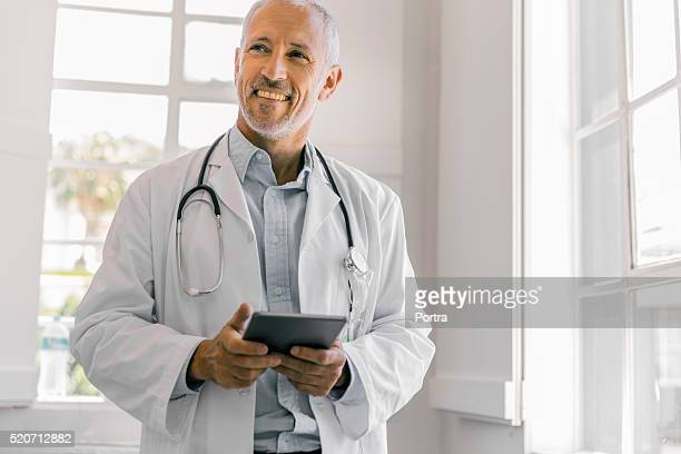 Cheerful doctor holding digital tablet in clinic