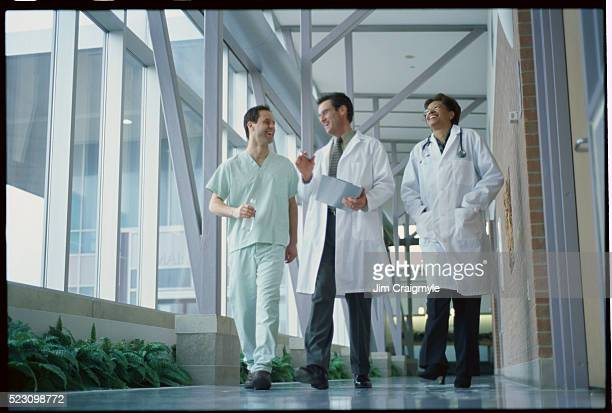Cheerful Doctors and Nurse Walking in Hallway