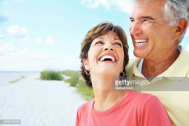 Cheerful elderly man and woman smiling on a beach