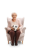 Cheerful elderly woman with a football sitting in an armchair and looking at the camera isolated on white background