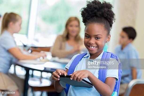 Cheerful elementary schoolgirl waits for class to start
