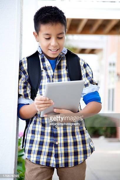 Joyeux Élève du primaire avec une tablette numérique
