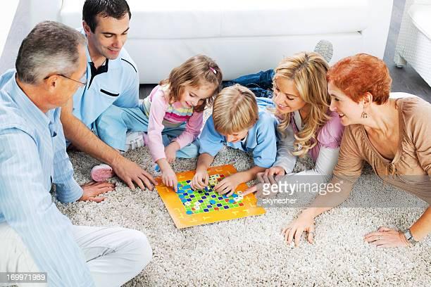Fröhliche Familie spielen Brettspiel auf dem Boden.