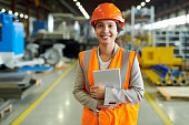 Waist up portrait of cheerful young woman wearing hardhat smiling happily looking at camera while enjoying work in production workshop, copy space