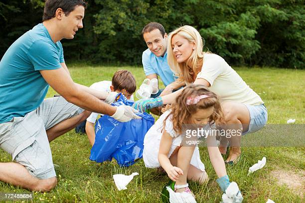 Cheerful Familes Picking Up Litter Outdoors.