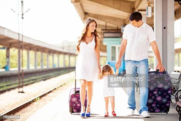 Fröhliche Familie am Bahnhof.