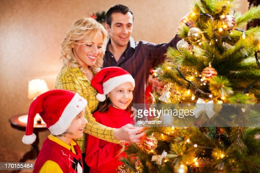 People Decorating For Christmas cheerful family decorating christmas tree stock photo | getty images