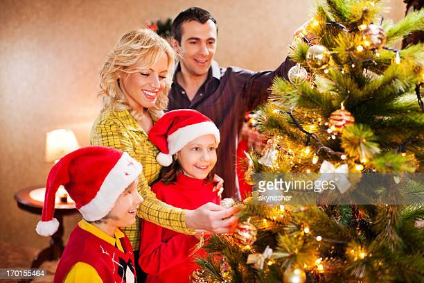 Cheerful family decorating Christmas tree.