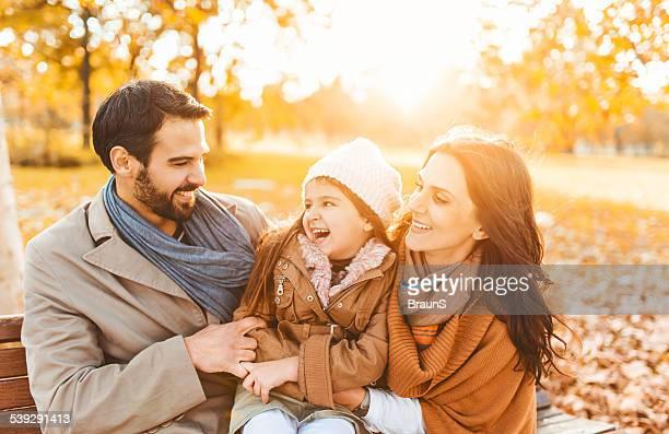 Joyeuse famille appréciant le jour de l'automne au coucher du soleil.