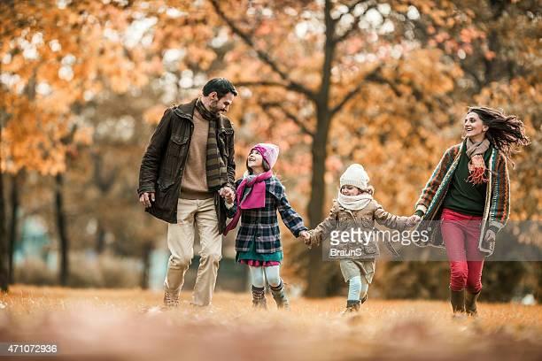 Fröhliche Familie Spaß im Herbst Tag beim Laufen.