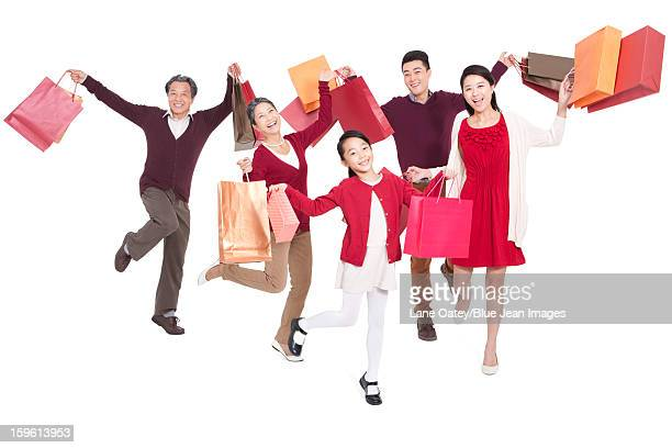 Cheerful family jumping in mid-air with shopping bags