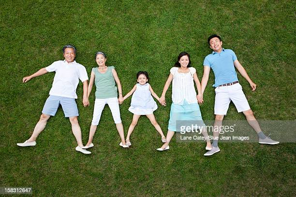 Cheerful family lying in a row on grass