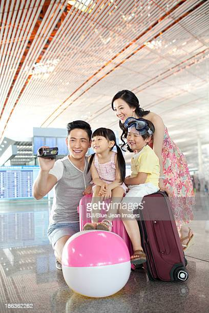 Cheerful family photographing at the airport