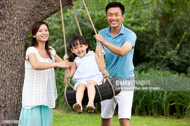 Cheerful family playing on a swing outdoors