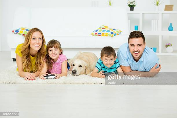 Cheerful family playing video game at home.