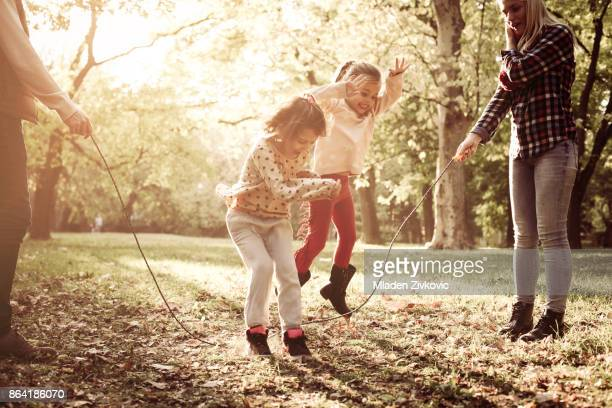 Cheerful family playing with jump rope together in park.