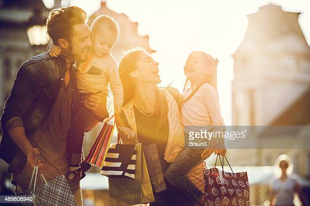 Cheerful family shopping in the city at sunset.