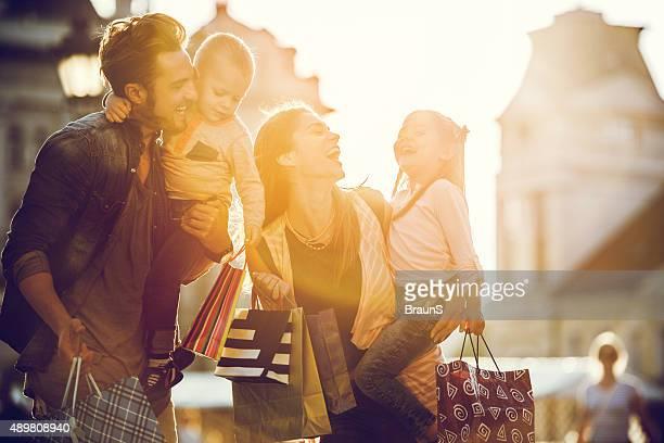Fröhliche Familie einkaufen in der Stadt bei Sonnenuntergang.