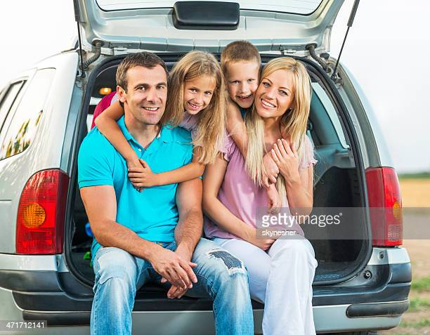 Cheerful family sitting in a car trunk outdoors.