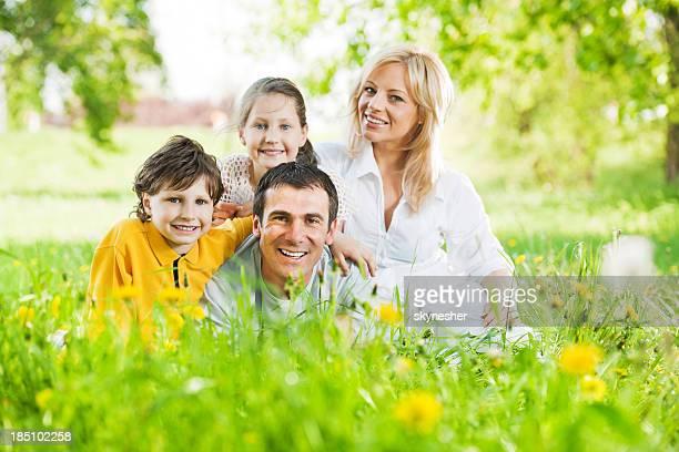 Joyeuse famille assis dans le champ de dandelions.