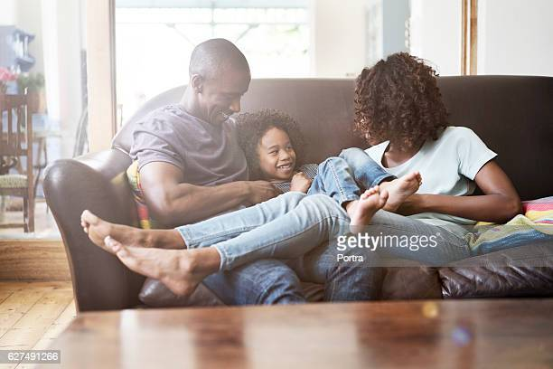 Cheerful family sitting on sofa at home