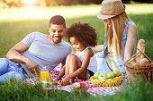 Cheerful family devoting time to picnic together on weekends