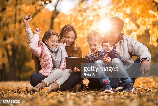 Cheerful family using digital tablet in autumn leaves. : Stockfoto
