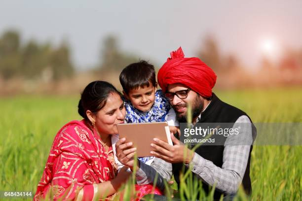 Cheerful Family using I pad in the green field