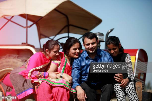 Cheerful family using laptop in the field