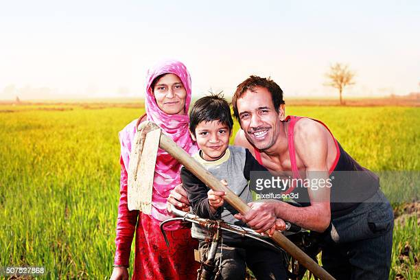 Cheerful Family with Bicycle standing in the field Portrait
